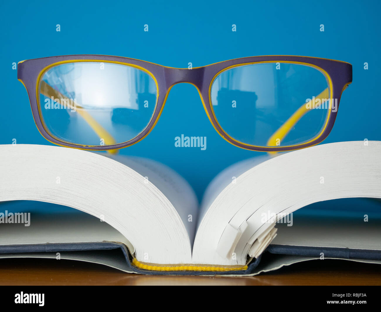 macro photo of reading glasses lay on top of opened book. education and learing concept Stock Photo