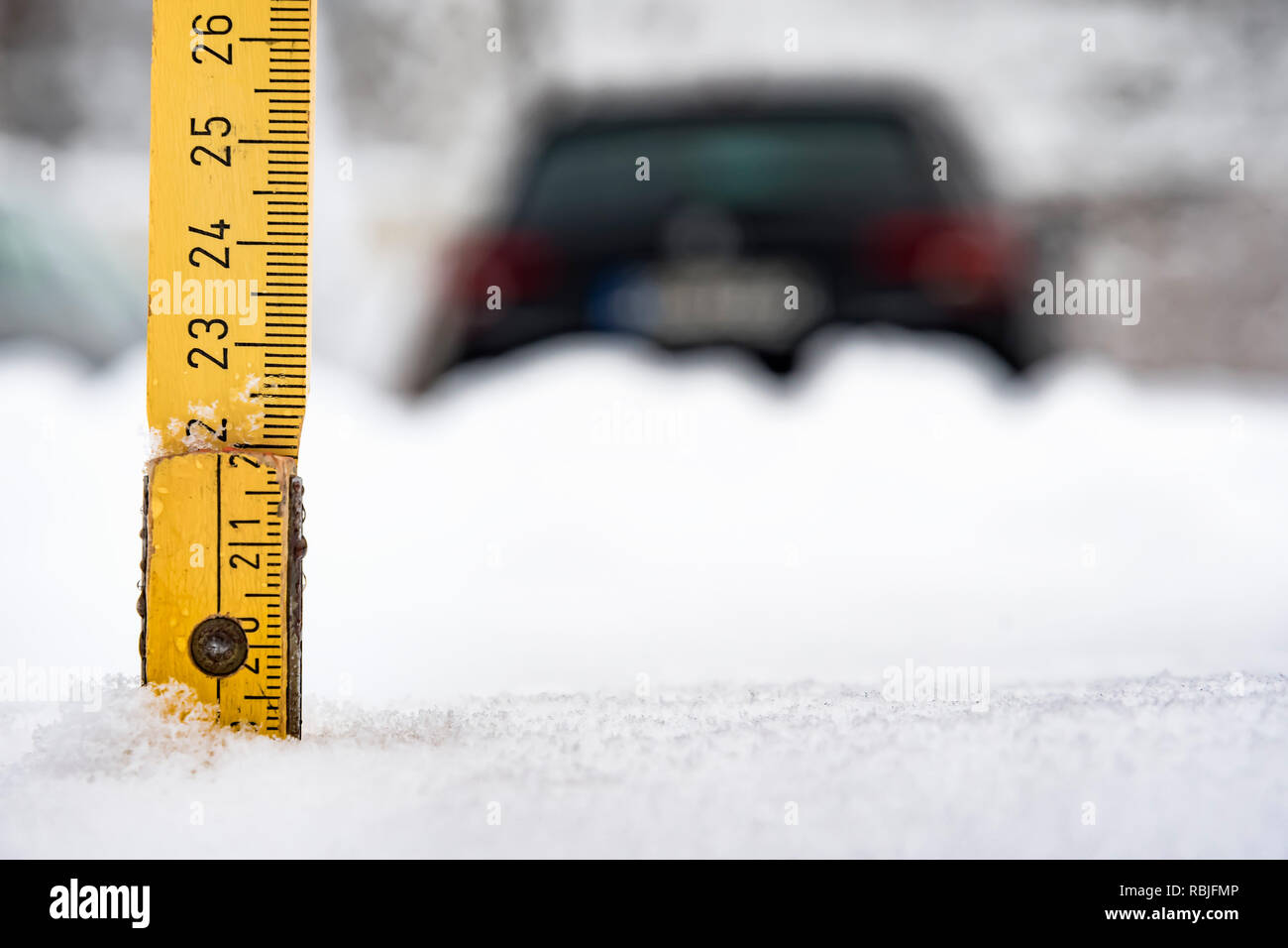 Yellow meter rule is stuck in a snow with car in background in winter in Bavaria, Germany - Stock Image
