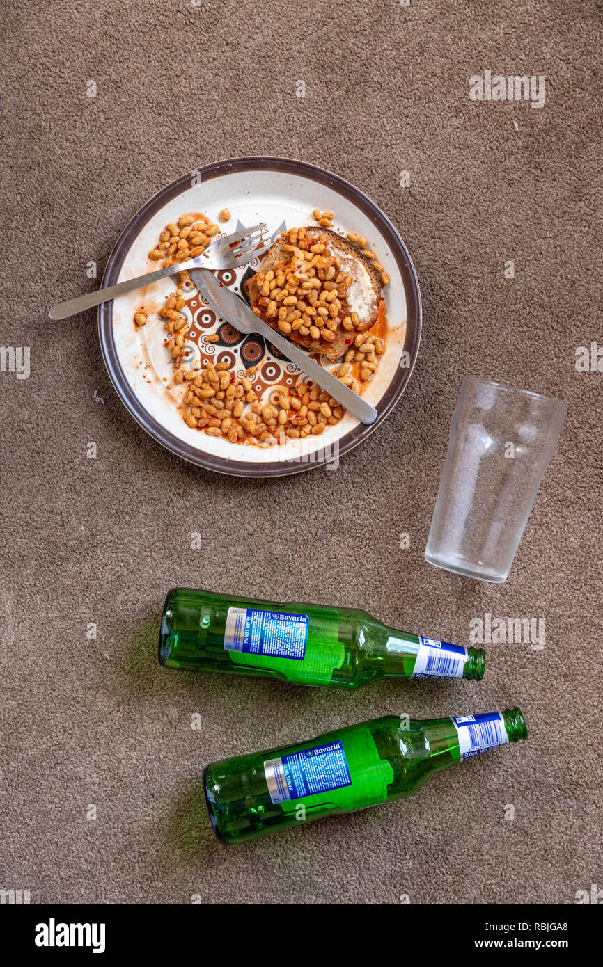The floor of a student flat - congealed baked beans - empty glass - beer bottles - Stock Image