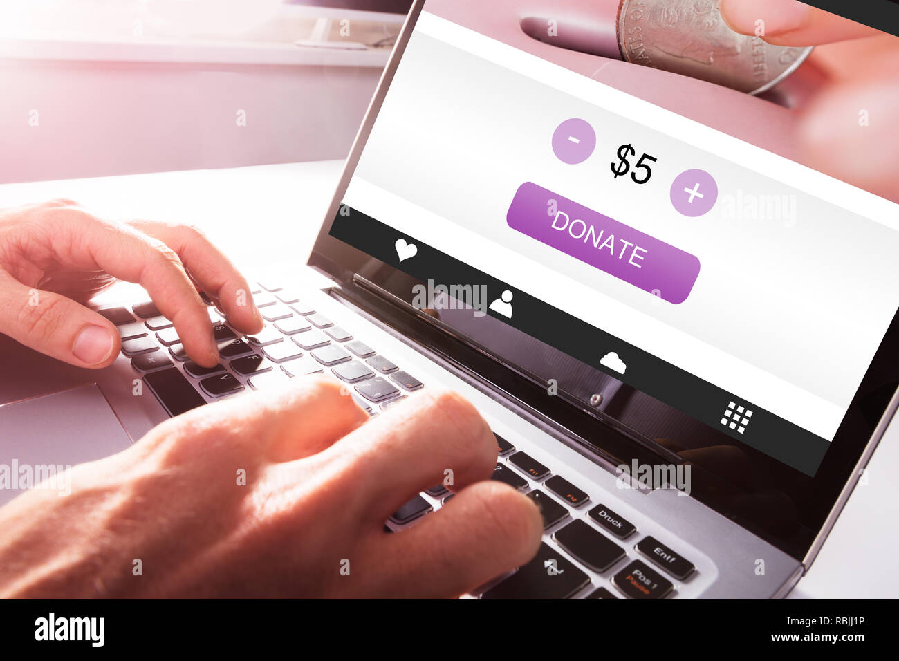 Close-up Of A Man's Hand Using Laptop To Donate Money - Stock Image