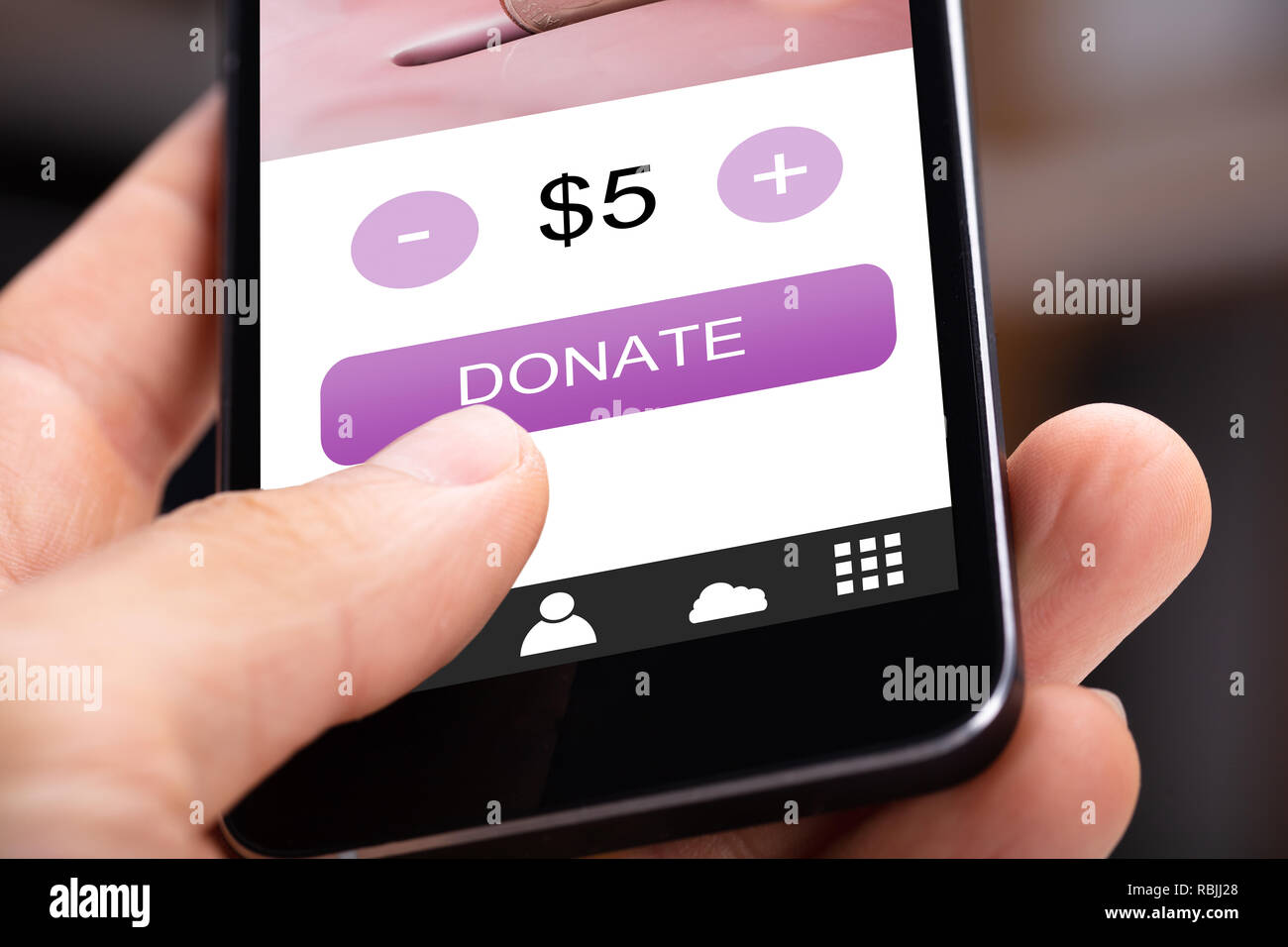 Close-up Of A Person's Hand Donating Money On Cellphone - Stock Image