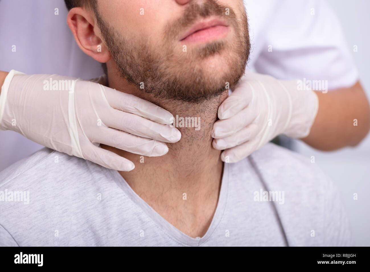Doctor's Hand Wearing Gloves Performing Physical Exam Palpation Of The Thyroid Gland Stock Photo