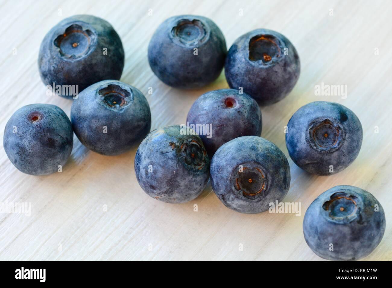 Close-up photo of fresh ripe blueberries on white wooden background - Stock Image