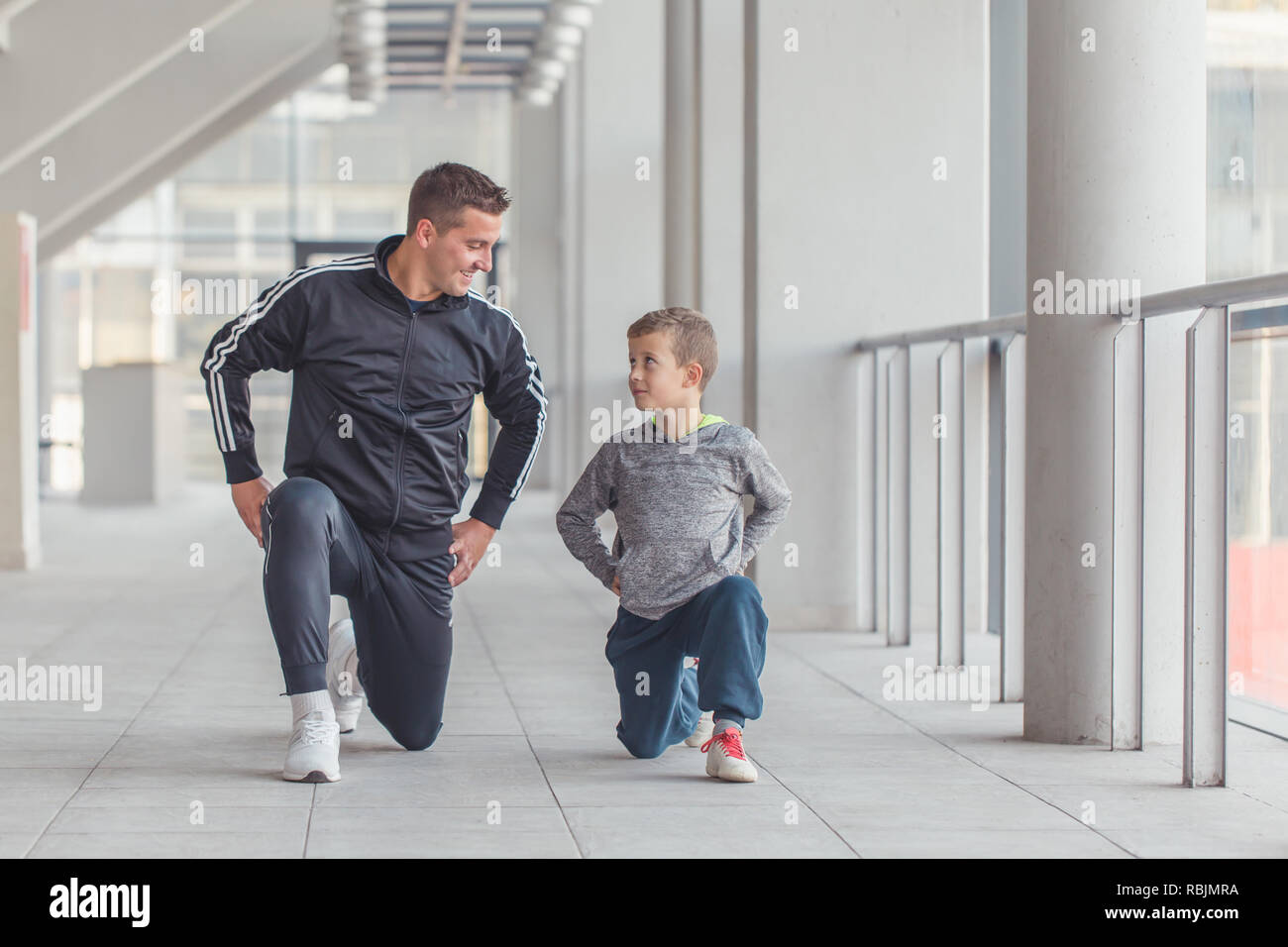 Little boy and his father doing stretching legs exercises  together at a sports center. Father and son spend time together and lead a healthy lifestyl - Stock Image