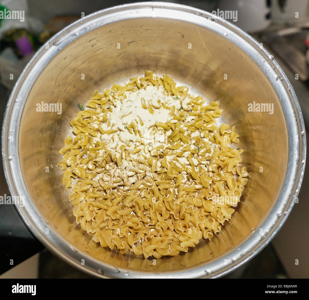 contents of Continental Pasta & Sauce Creamy Bacon Carbonara 85g satchel poured into a saucepan before adding water - Stock Image