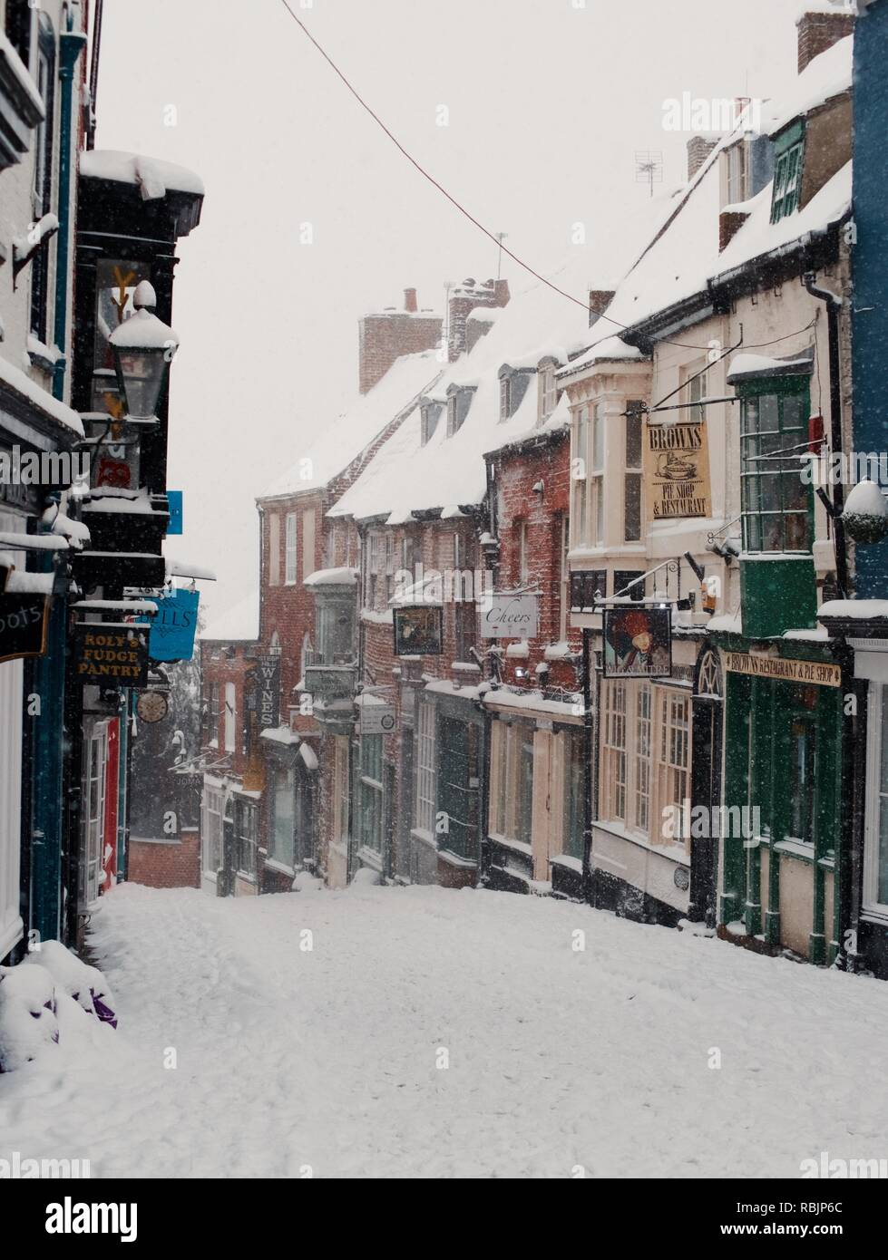 Top of Lincoln Steep Hill with Shop fronts during heavy snowfall 2018 (March) - Stock Image