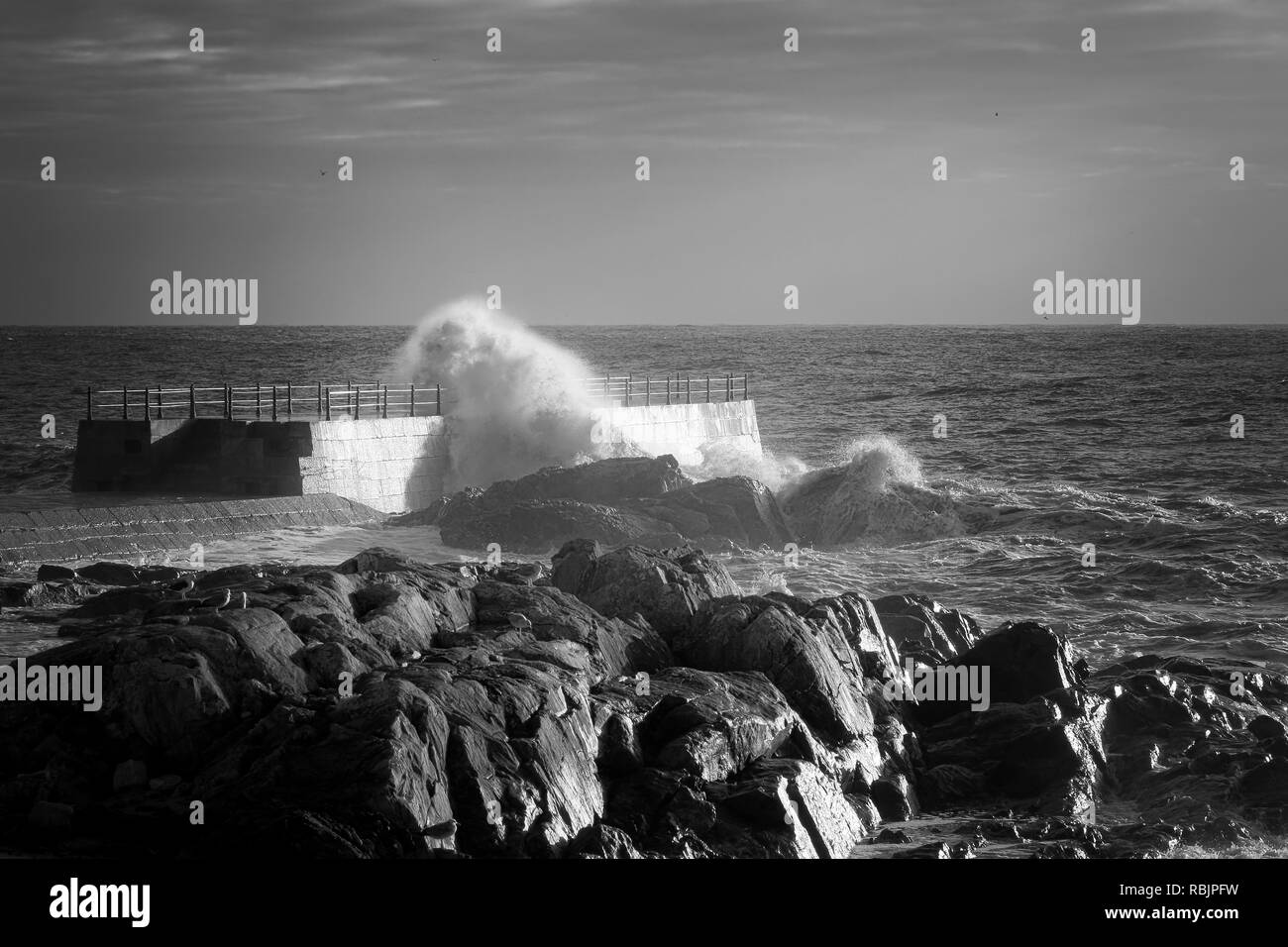 Black and white seascape with pier and rocks. Used infrared filter. Stock Photo