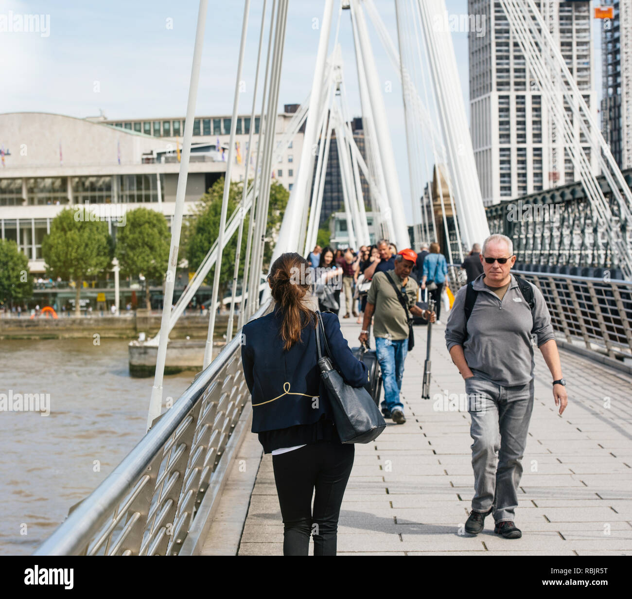 LONDON, UNITED KINGDOM - MAY 18, 2018: Pedestrians walking on a warm sunny day on the Hungerford Bridge in London - Stock Image