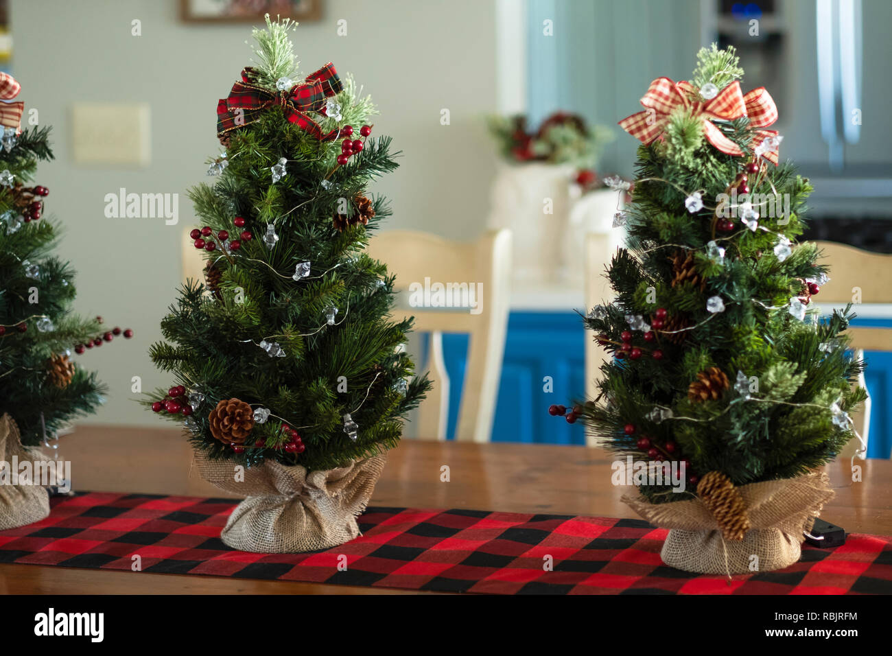 Three Minature Tabletop Christmas Trees With Burlap On A Red And Black Table Runner Indoor Christmas Decor Stock Photo Alamy
