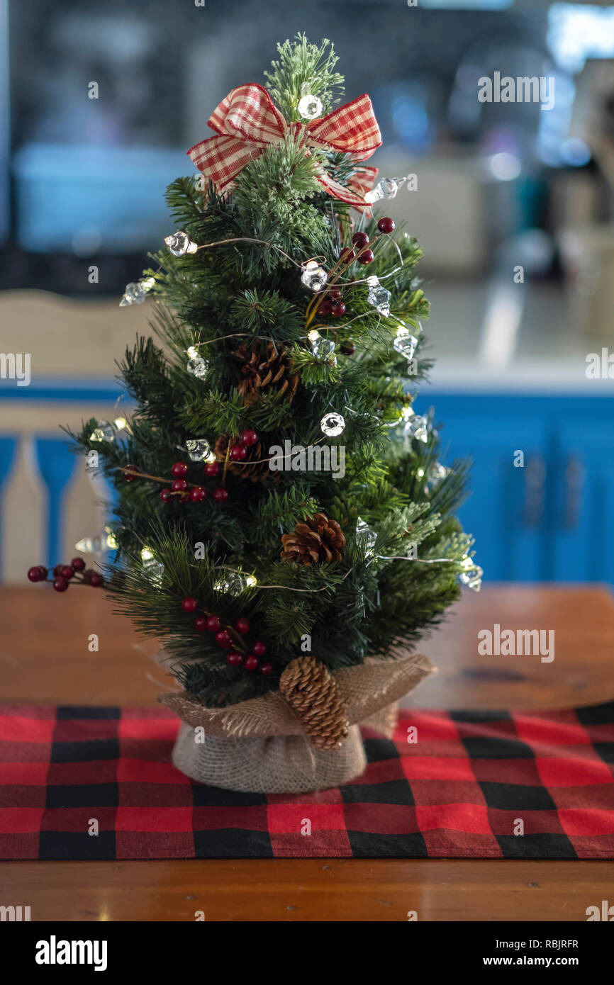 A Minature Tabletop Christmas Tree With Burlap On A Red And Black Table Runner Indoor Christmas Decor Stock Photo Alamy