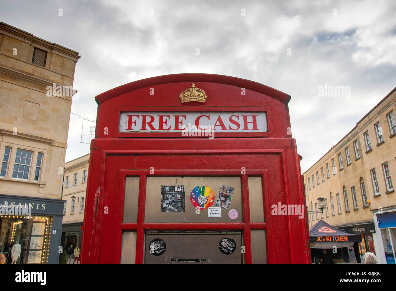 Old red telephone box now used as a cash machine in Bath, England, UK - Stock Image