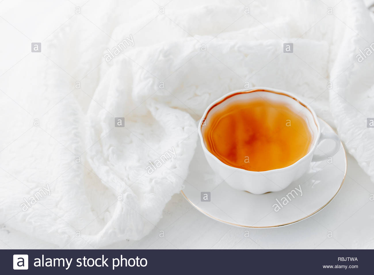 Tea in white cup with white knitted scarf. Hot morning tea drink background with copy space. Highkey image of tea - Stock Image