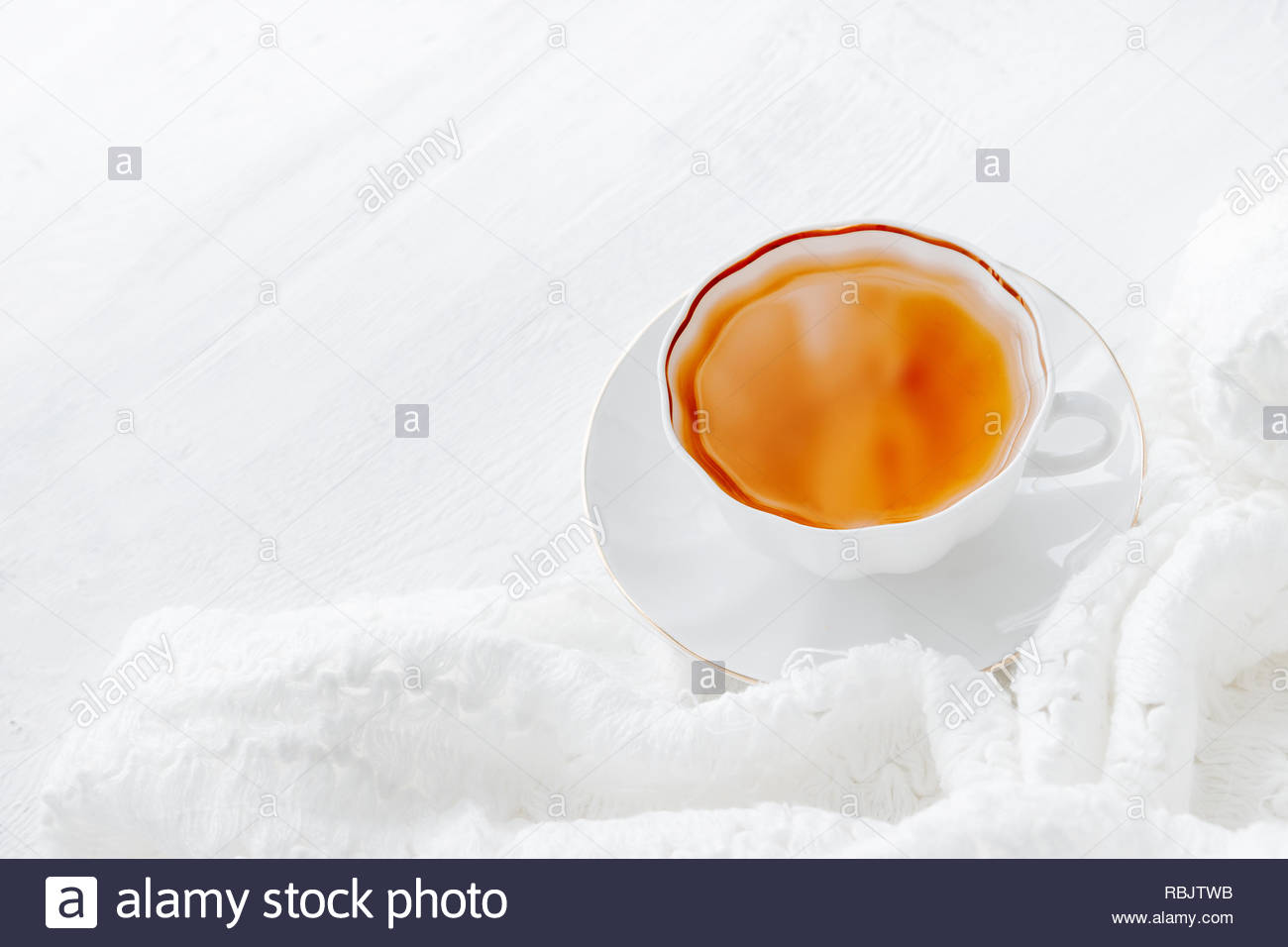 Tea in white cup with white knitted plaid. Hot morning tea drink background with copy space. Highkey image of tea - Stock Image