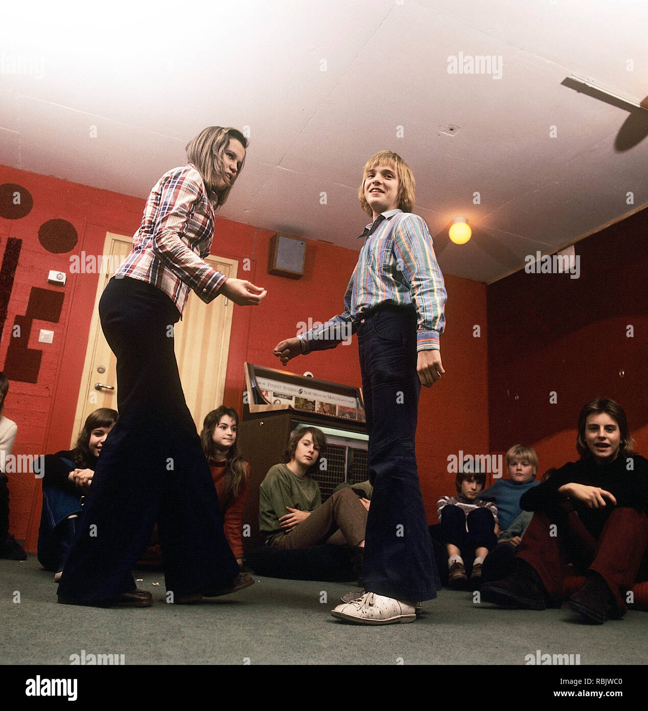 Teenage party in the 1970s. A group of teenagers have arranged a party and a boy and a girl is dancing to the music from the jukebox. Notice the wide legged jeans type that was typical of the decade. Sweden 1970s. Photo Kristoffersson Stock Photo