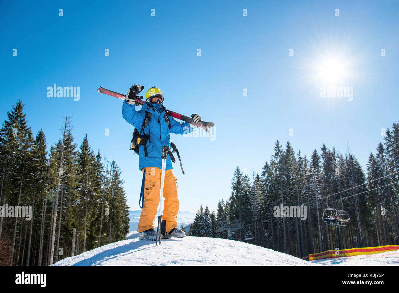 Full length shot of a skier standing on top of a snowy slope in the mountains, raising his arms in the air, enjoying beautiful sunny winter day at winter resort - Stock Image