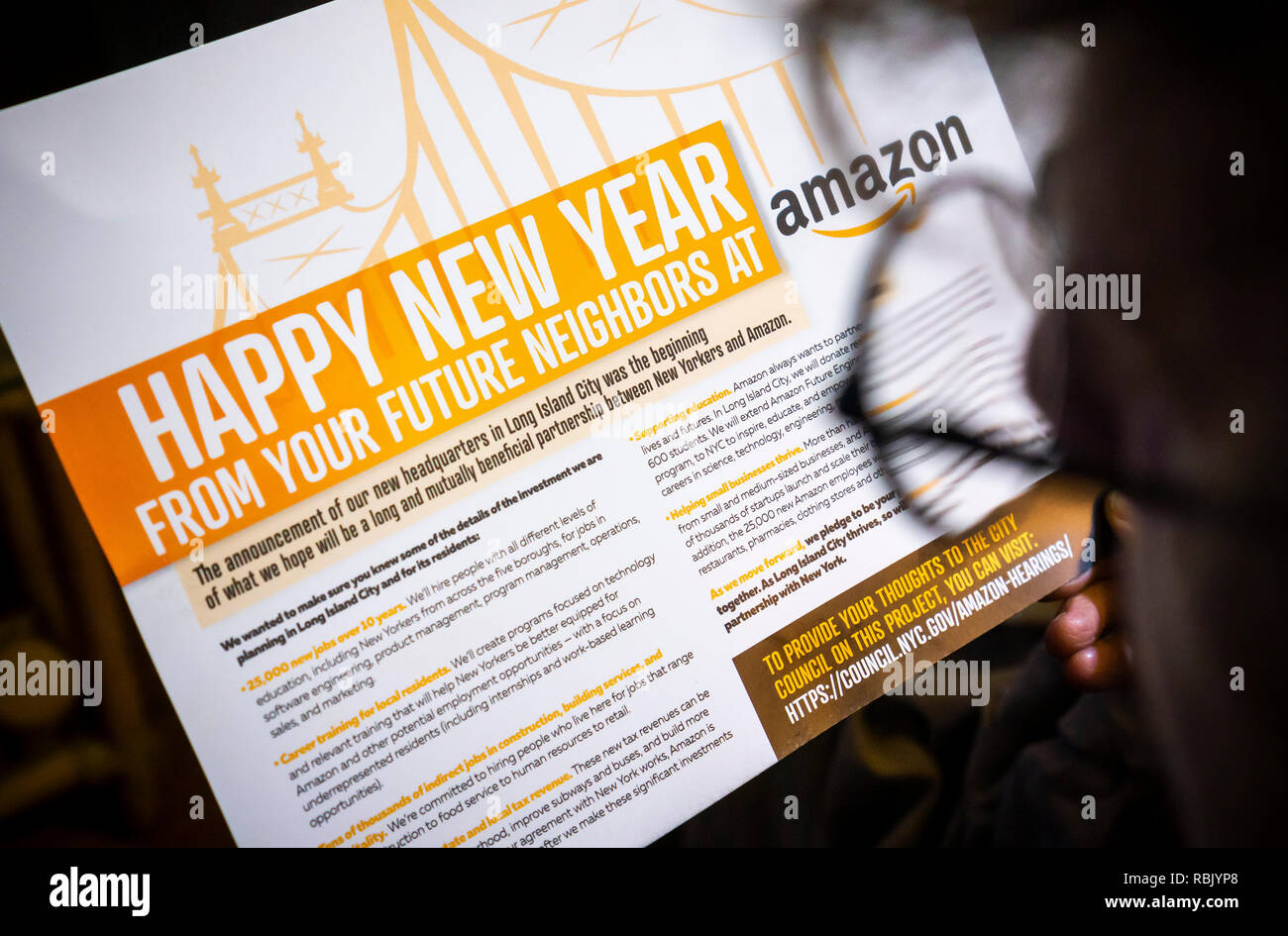 A woman in New York looks at a mailing she received from Amazon on Tuesday, January 8, 2019 touting the benefits of 'Amazon is investing in Long Island City' related to their building their 'HQ 2' in the Queens neighborhood. (© Richard B. Levine) - Stock Image