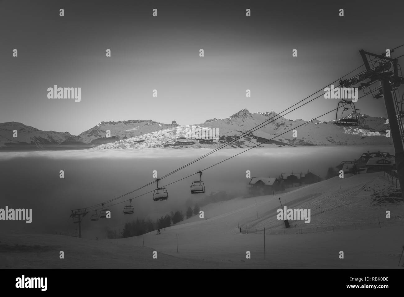 A black and white of a chairlift rising out of a lake of cloud - Stock Image