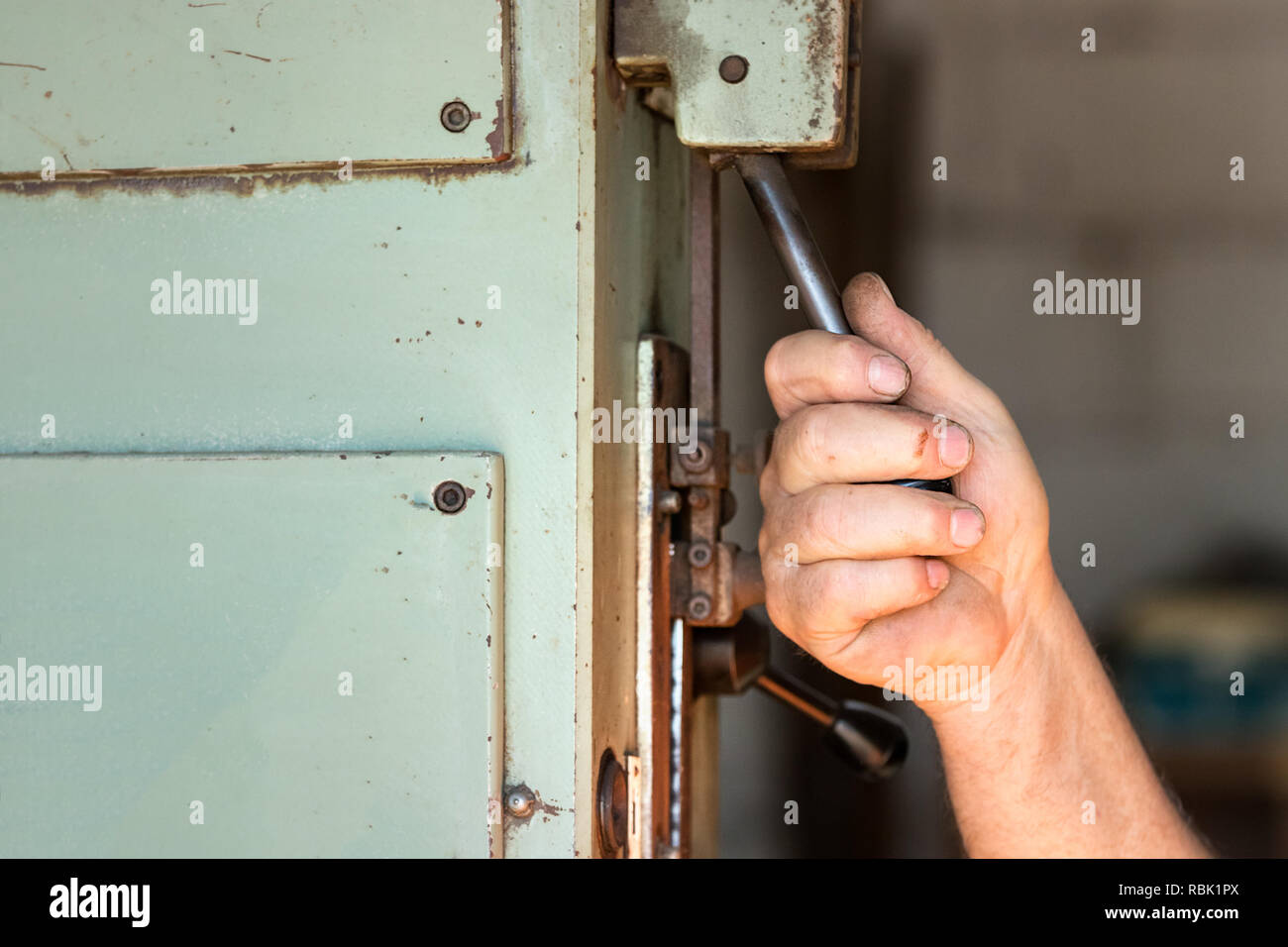 A male worker operating an industrial toggle switch. - Stock Image