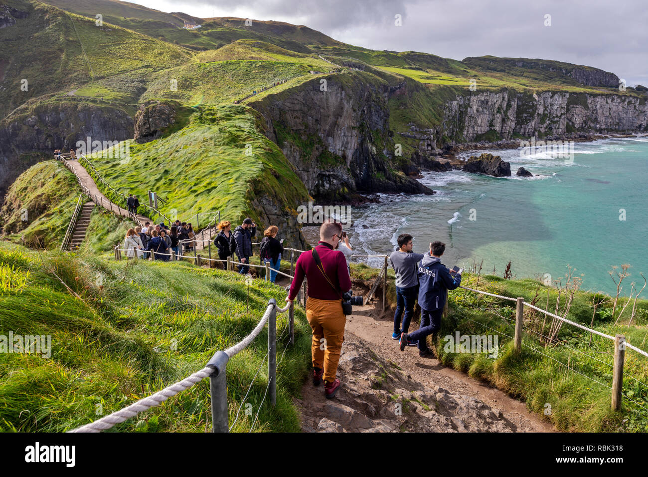 Tourists and visitors explore and walk across the Rope Bridge at Carrick-A-Rede and Larrybane Bay on the West Coast of Ireland. - Stock Image