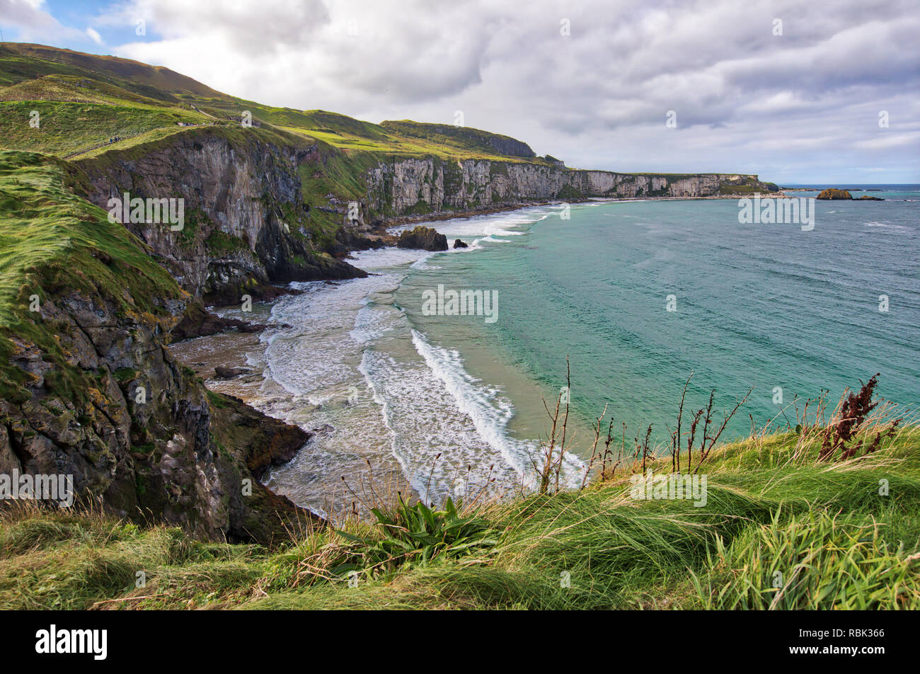 Tourists and visitors explore and walk across the Rope Bridge at Carrick-A-Rede and Larrybane Bay on the West Coast of Ireland. Stock Photo