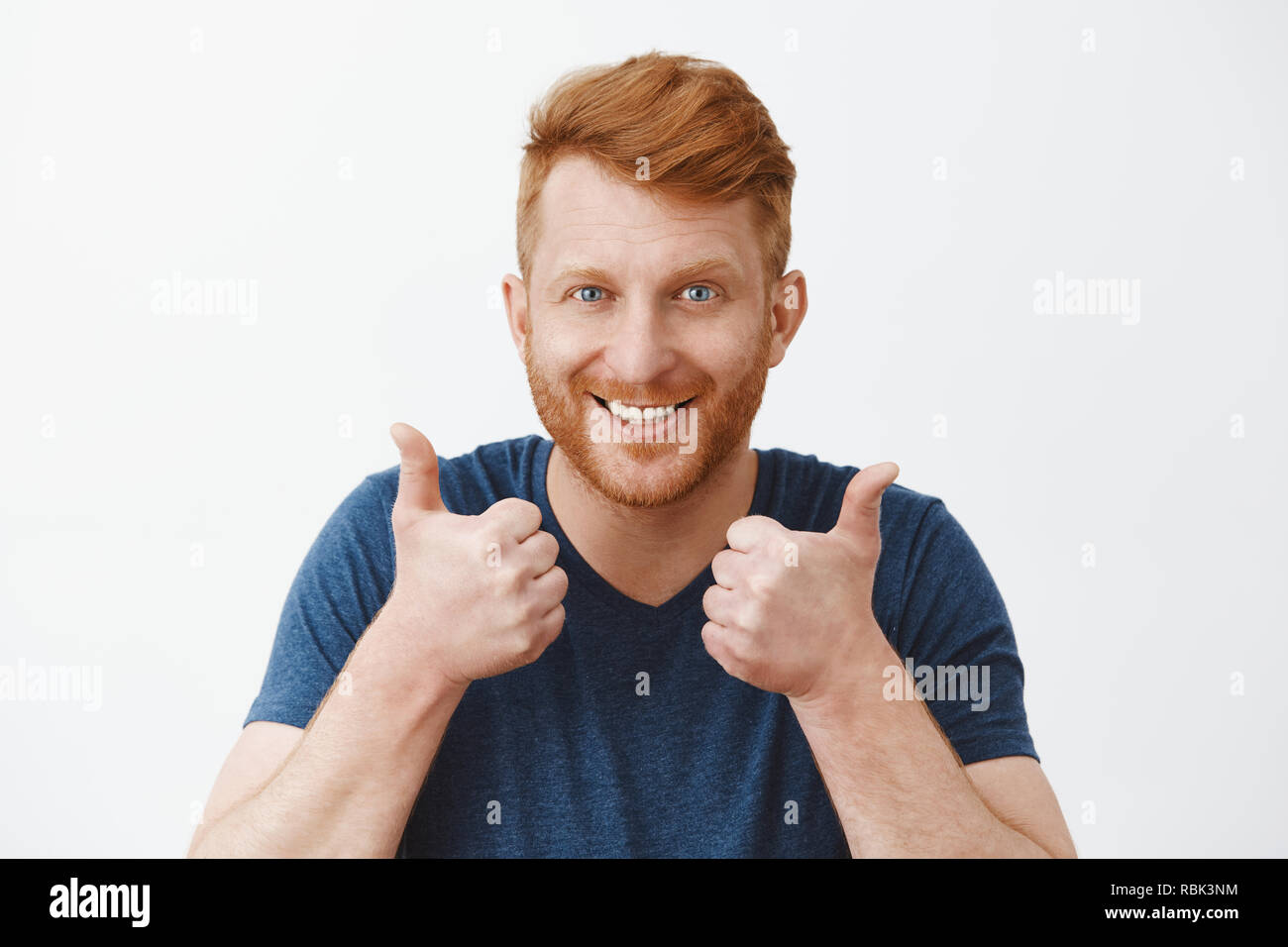 Supportive and attractive adult redhead male with bristle liking great plan raising hands, showing thumbs up, smiling joyfully, accepting nice idea or cheering friend who trying talk to charming woman - Stock Image