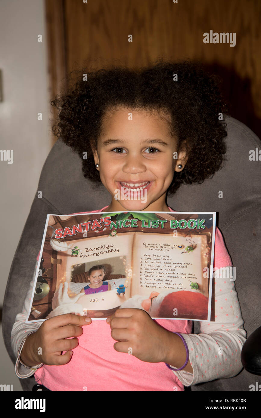 Vadnais Heights, Minnesota. Bi-racial child showing her name on Santa's nice list. - Stock Image