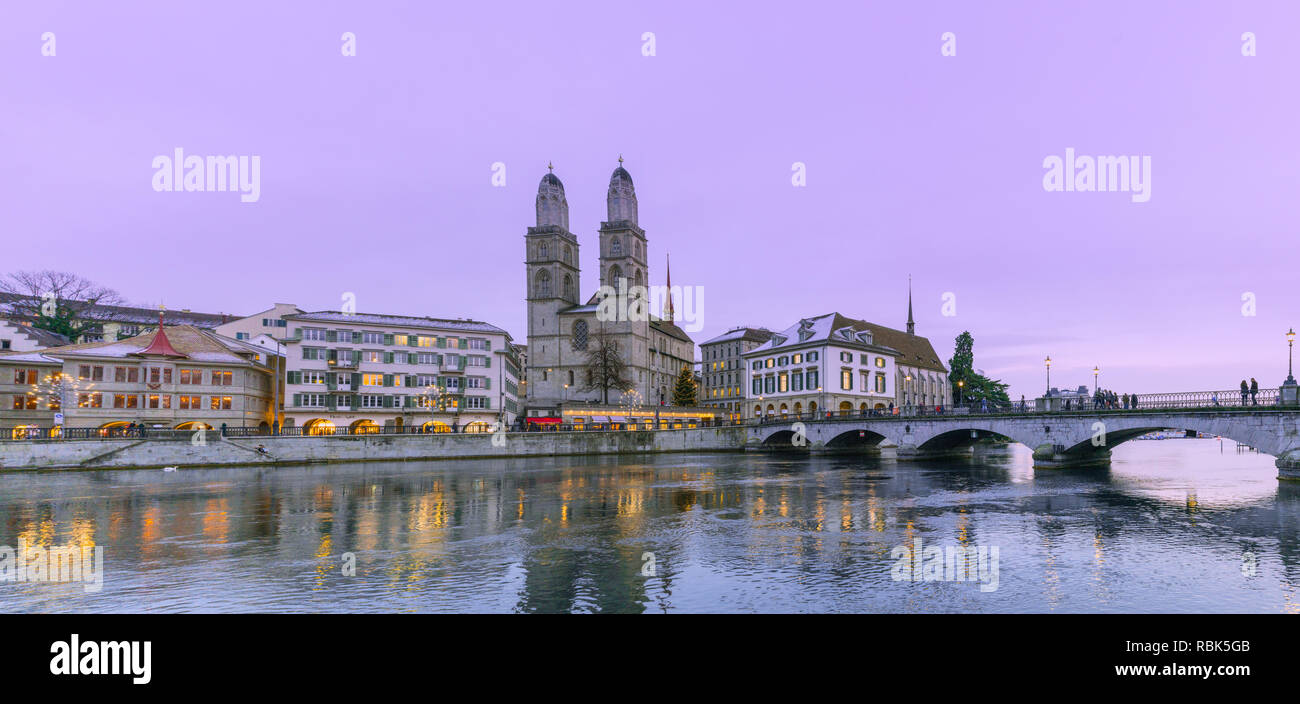 Zurich, ZH / Switzerland - January 4, 2019: Zurich skyline with Grossmuenster under a purple winter evening sky with many pedestrians crossing the Gro - Stock Image