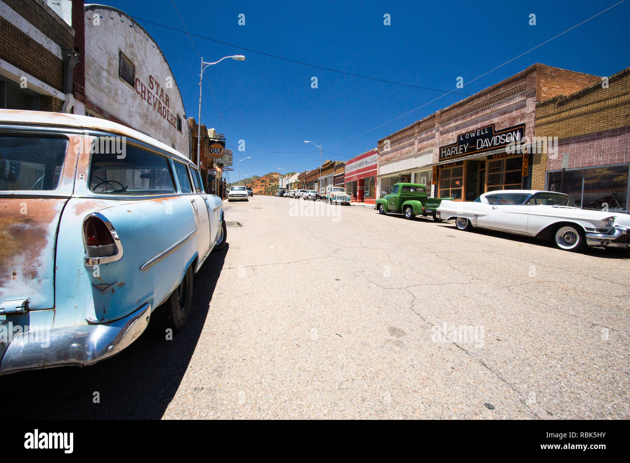 Bisbee, AZ, USA / 12 July 2016: historic ghost town of Lowell with the carefully renovated Erie street lined with cars and American culture icons - Stock Image