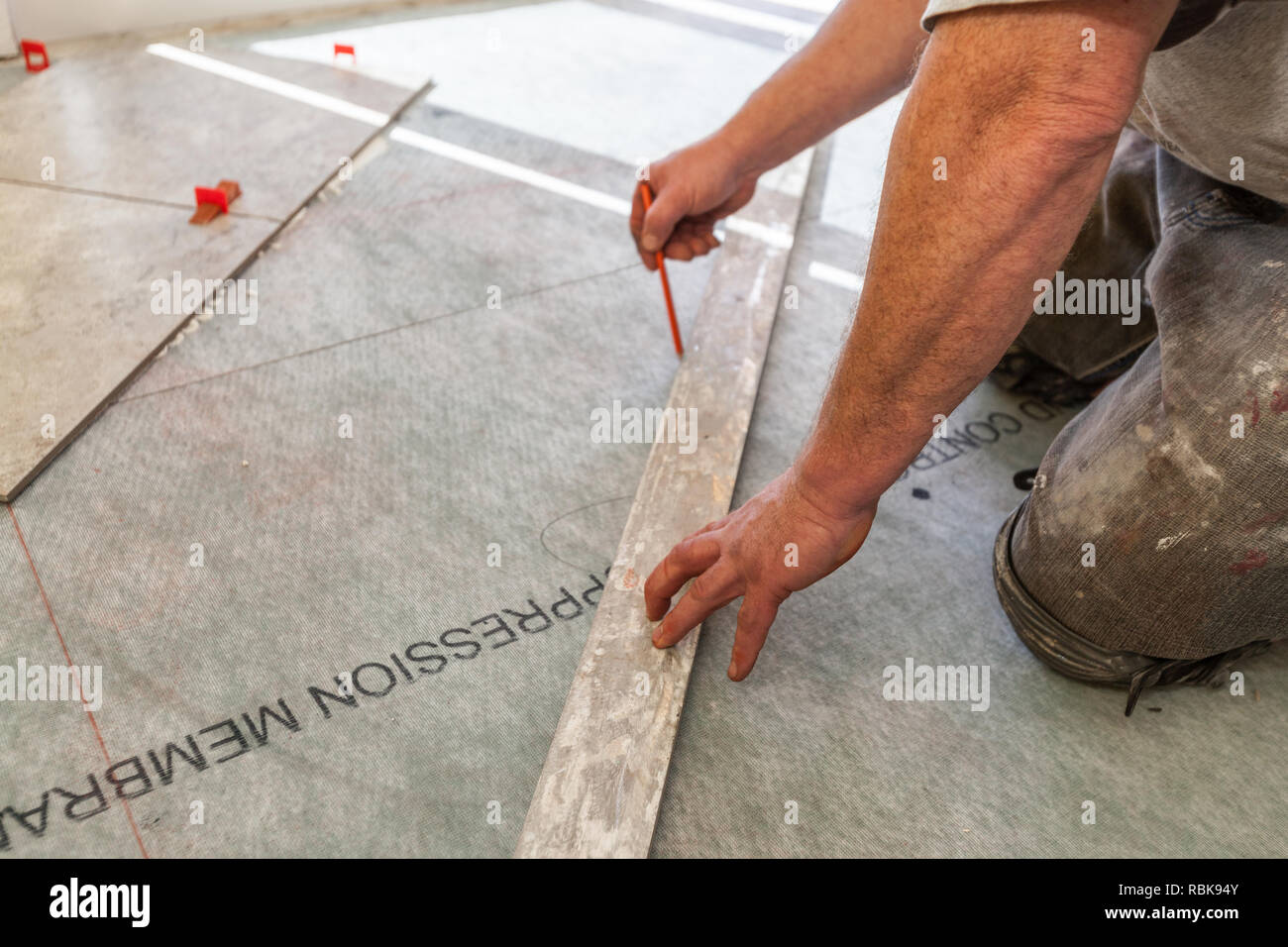 Man Using Marking Pencil To Draw Tile Grid On Floor - Stock Image