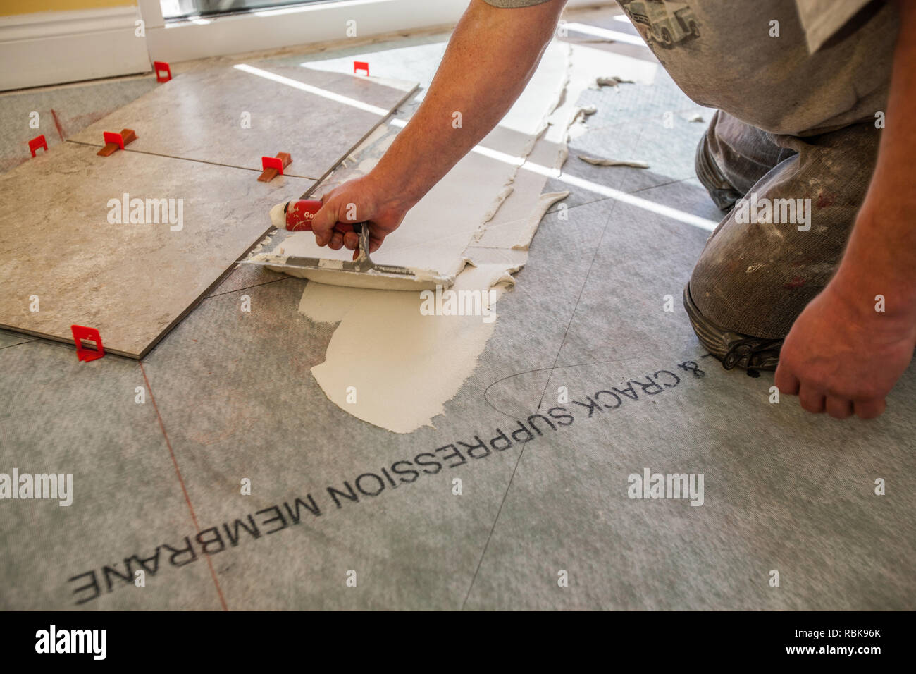 Man Using Trowel To Spread Tile Adhesive - Stock Image