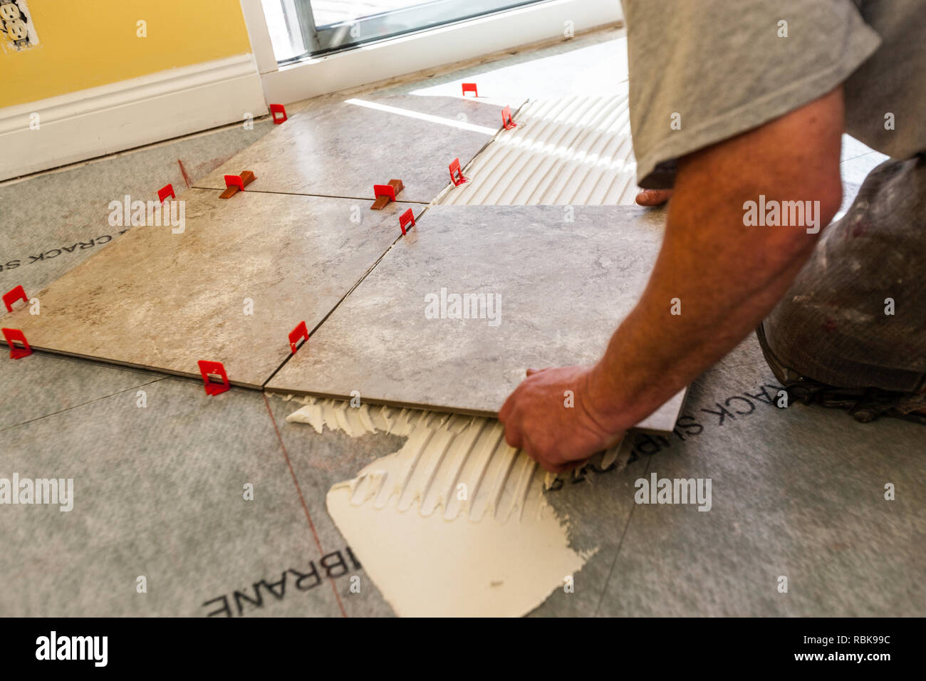 Man Laying Piece Of Square Tile On Adhesive - Stock Image