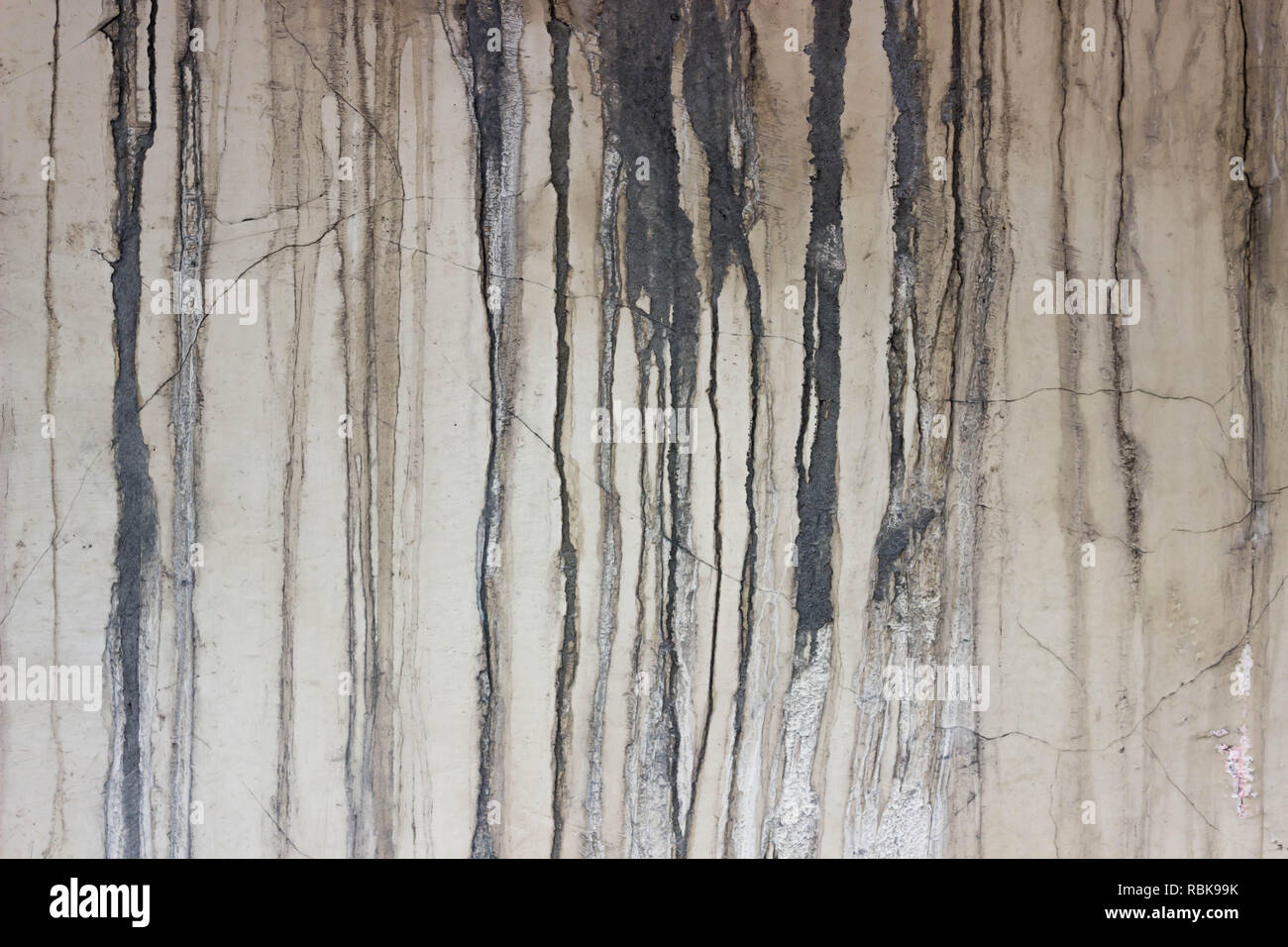 Grunge concrete wall with crack and stains in industrial building. Cement texture for design and background, with drips - Stock Image