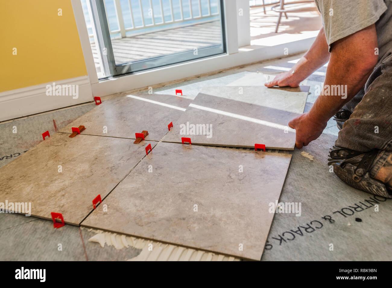 Man Laying Square Tile On Adhesive - Stock Image