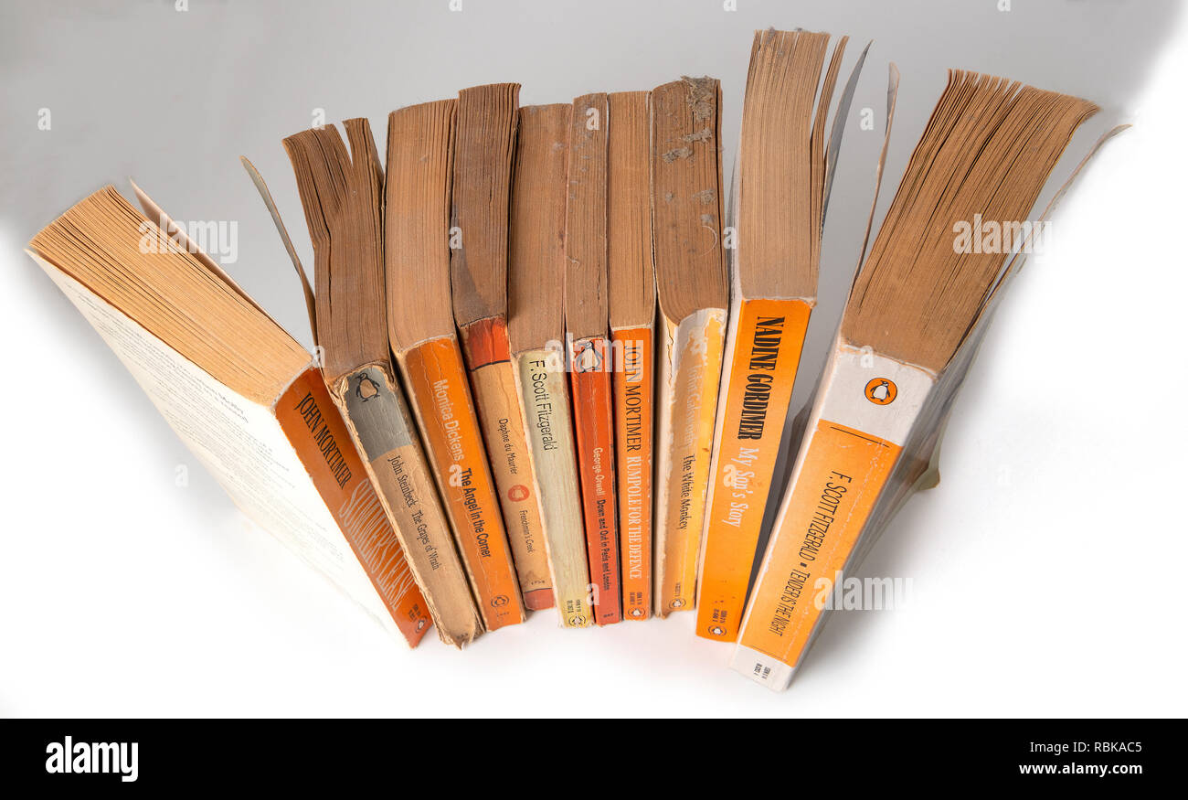 Collection of Penguin paper back books gathering dust from being left on a book shelf  for 20 years.  Berkshire, UK Stock Photo