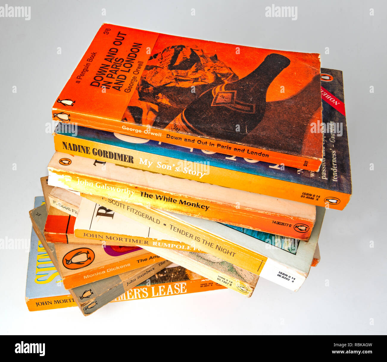 Collection of Penguin paper back books gathering dust from being left on a book shelf  for 20 years . - Stock Image