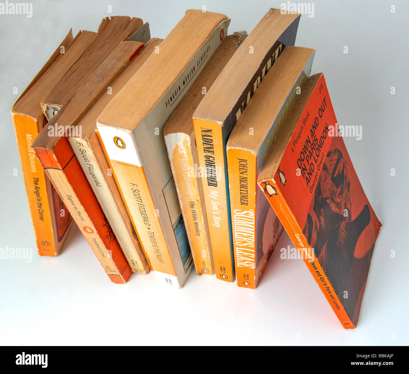 Collection of Penguin paper back books gathering dust from being left on a book shelf  for 20 years . Stock Photo