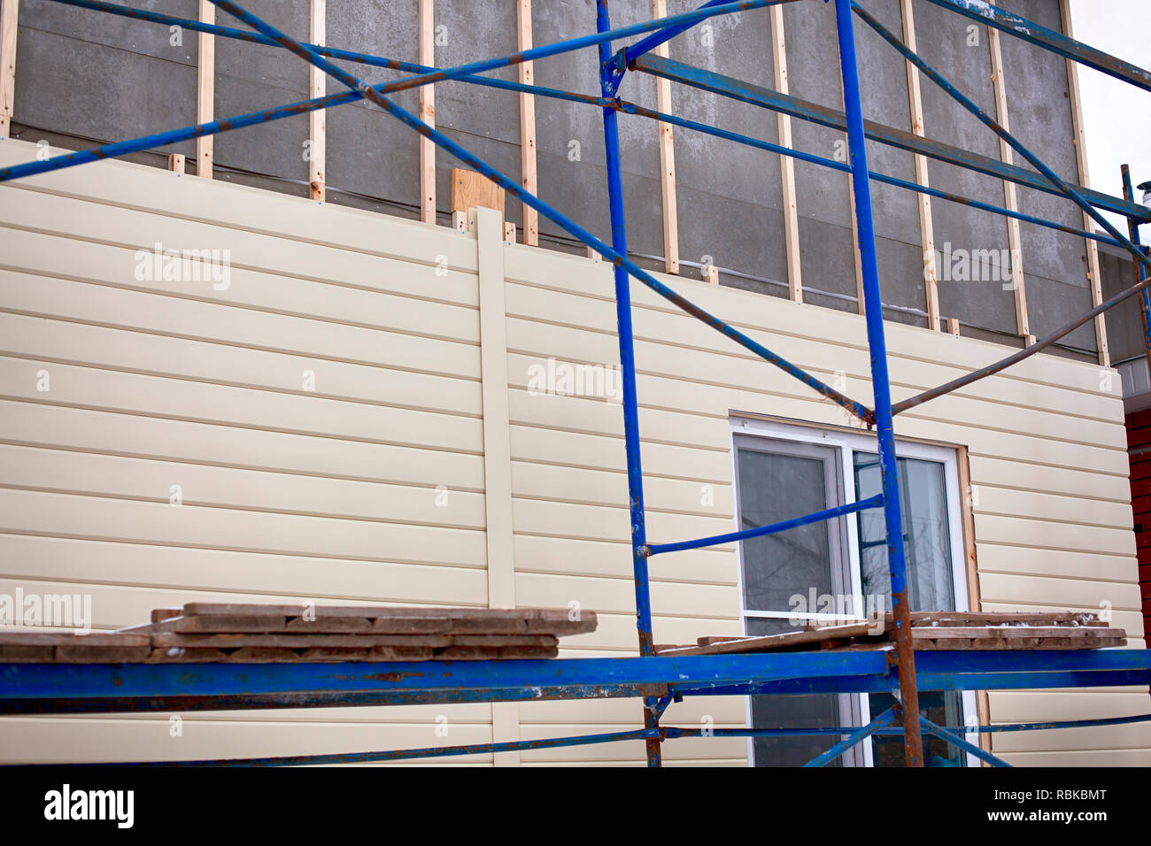 Scaffolding around house with beige siding covering the wall. Close-up. - Stock Image
