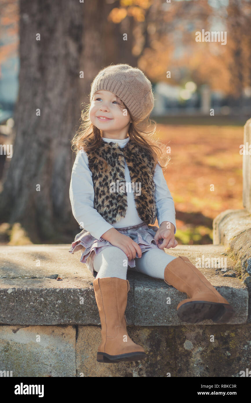 Dolly pin-up toothsome young brunette girl wearing fashion stylish gray jacket jerkin and warm hat with awesome boots clothes posing autumn spring par - Stock Image