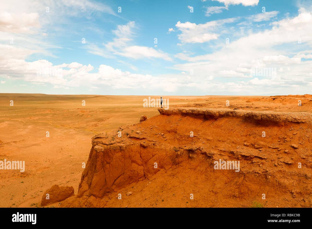 Traveller overseeing the endless Gobi Desert from Bajandsag (Flaming Cliffs) on a beautiful summer day (Gobi Desert, Mongolia, Asia) - Stock Image