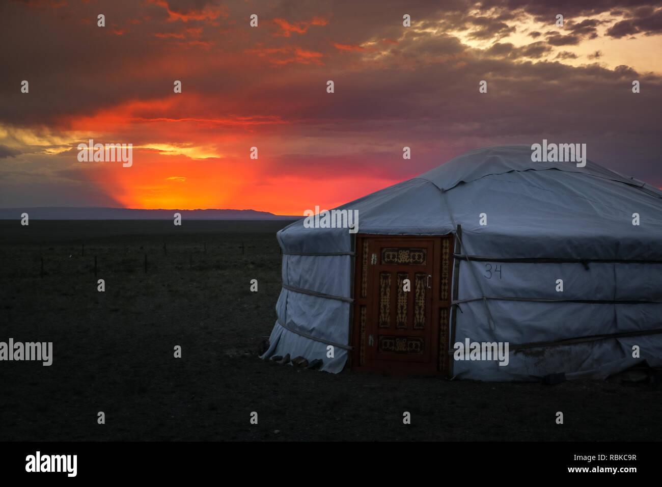 Traditional Mongolian housing / yurt at sunset with dramatic cloudy sky in the Gobi Desert near the Flaming Cliffs (Bajandsag, Gobi Desert, Mongolia) Stock Photo