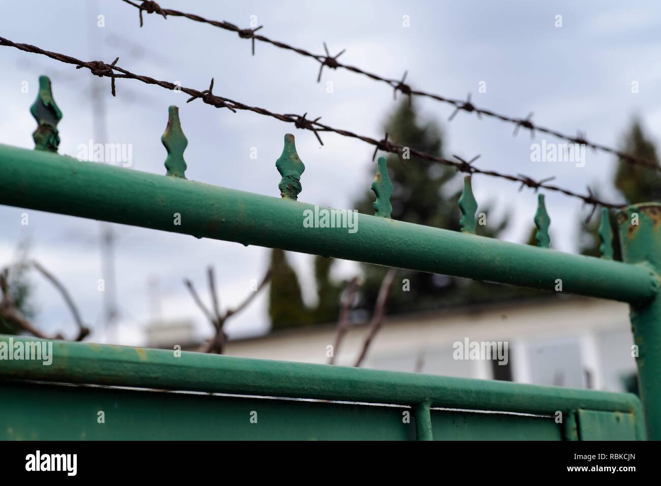 Barbed wire on the fence.Metal fence with barbed wire, guarded object. - Stock Image