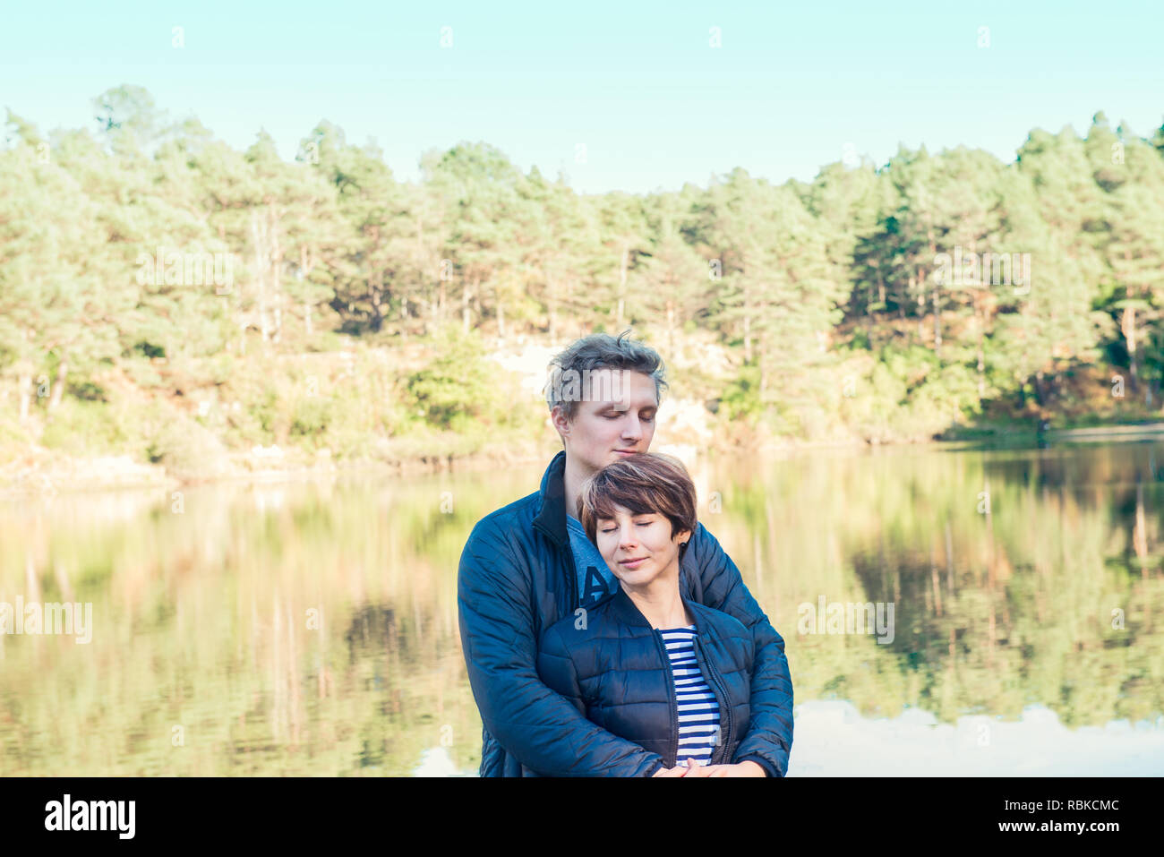 Two attractive dreamy people, couple in casual outfit at wild forest near water. Idyllic calm peaceful life style person freedom concept. Selective fo Stock Photo