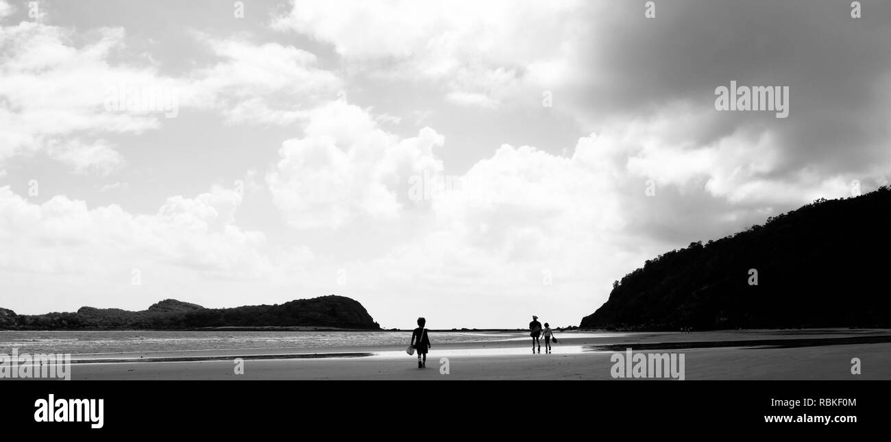 People walking on a sandy beach in  black and white, Hiking through Cape Hillsborough National Park, Queensland, Australia - Stock Image