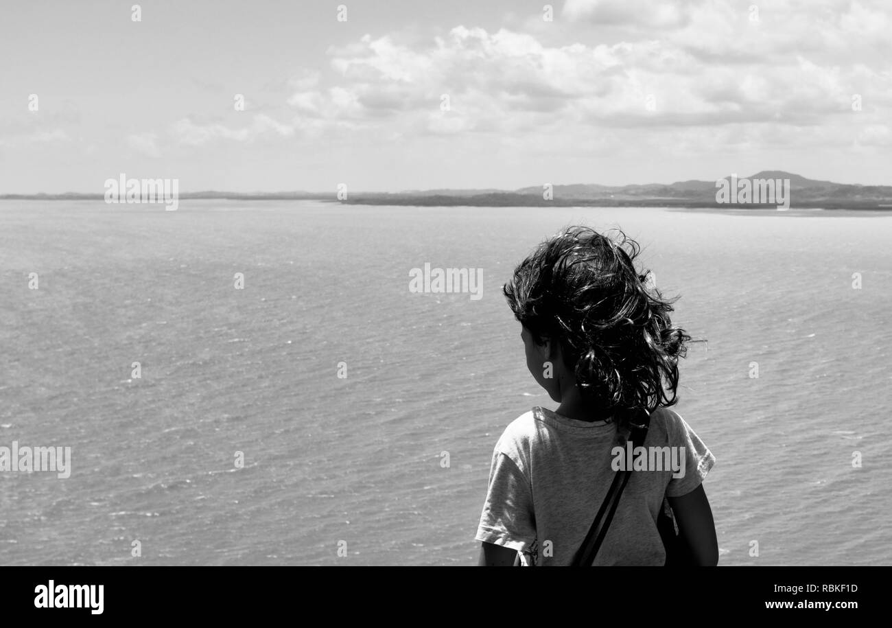 Girl standing looking over the sea with wind blowing through hair, Hiking through Cape Hillsborough National Park, Queensland, Australia - Stock Image