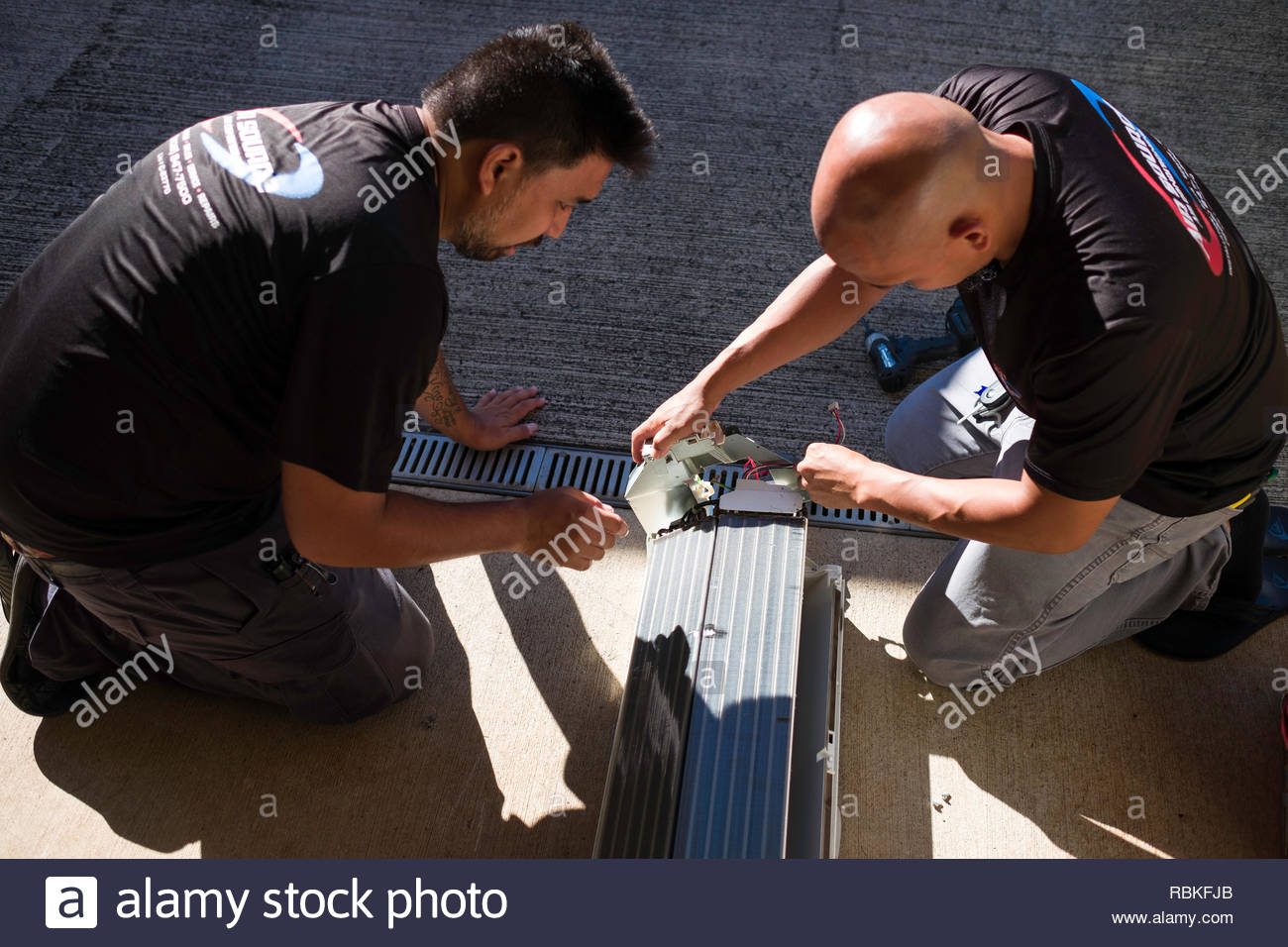 Two men disassembling ductless air condition unit, Honolulu, Oahu, Hawaii, USA - Stock Image