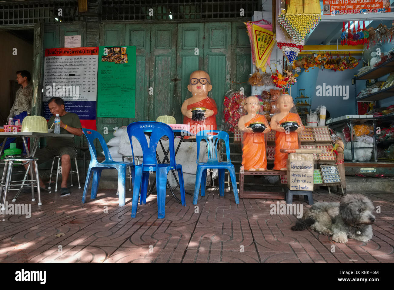 Atreet scene in Mahachai Rd., Bangkok, Thailand: a food stall and a shop selling Buddhist paraphernalia including monks' figures, guarded by a poodle - Stock Image