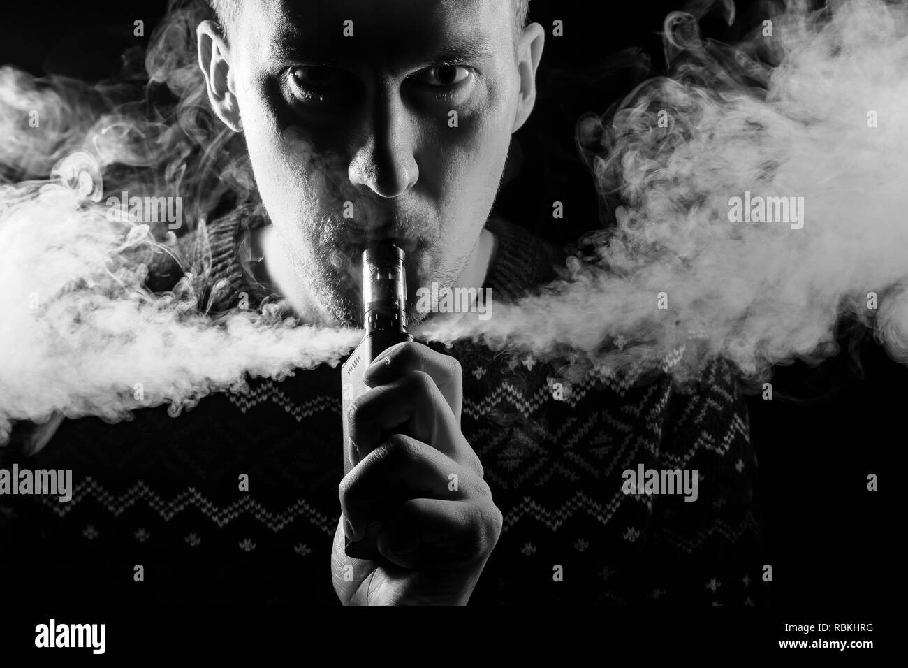 Portrait of a boy with a shadow on a serious face  with a colored backlight of monochrome smoking a vape and exhaling white smoke in different directi - Stock Image