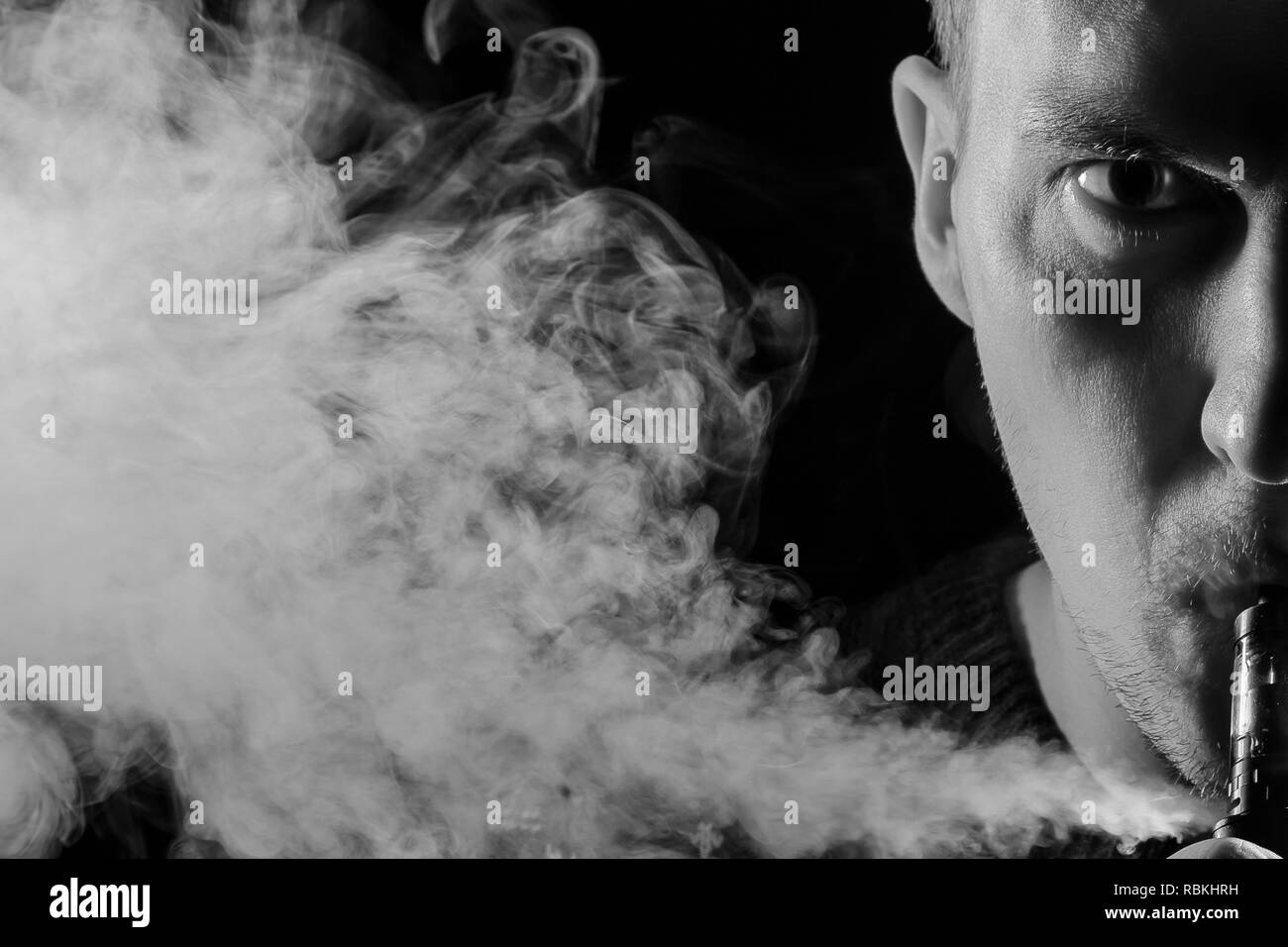Portrait of a half part of guy with a shadow on a serious face  with a colored backlight of monochrome smoking a vape and exhaling white smoke in diff Stock Photo