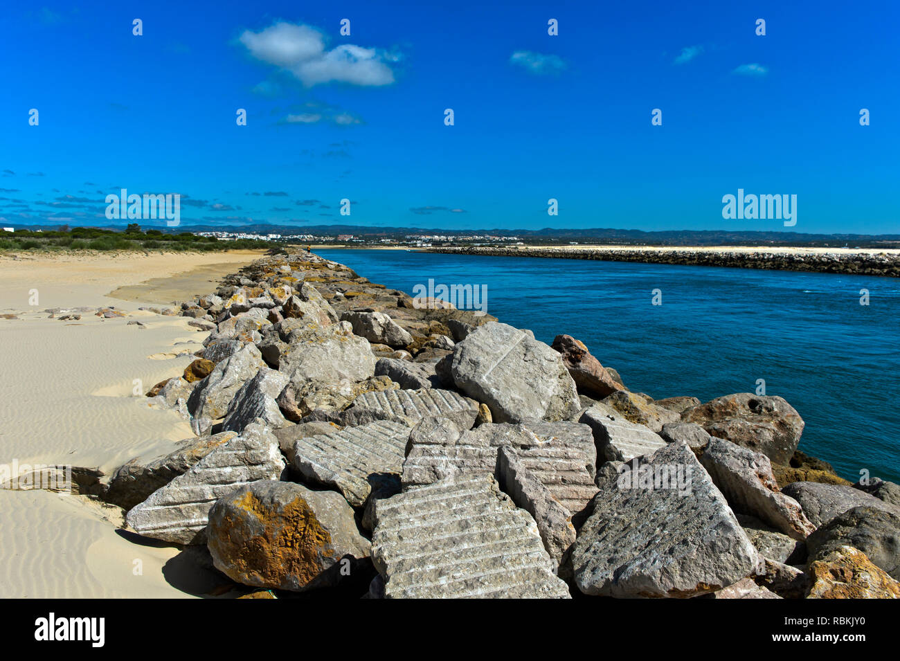 Boulders as protection of the litoral zone against rising sea levels at the mouth of the Gilao River, Tavira Island, Ilha de Tavira, Tavira, Algarve,  - Stock Image