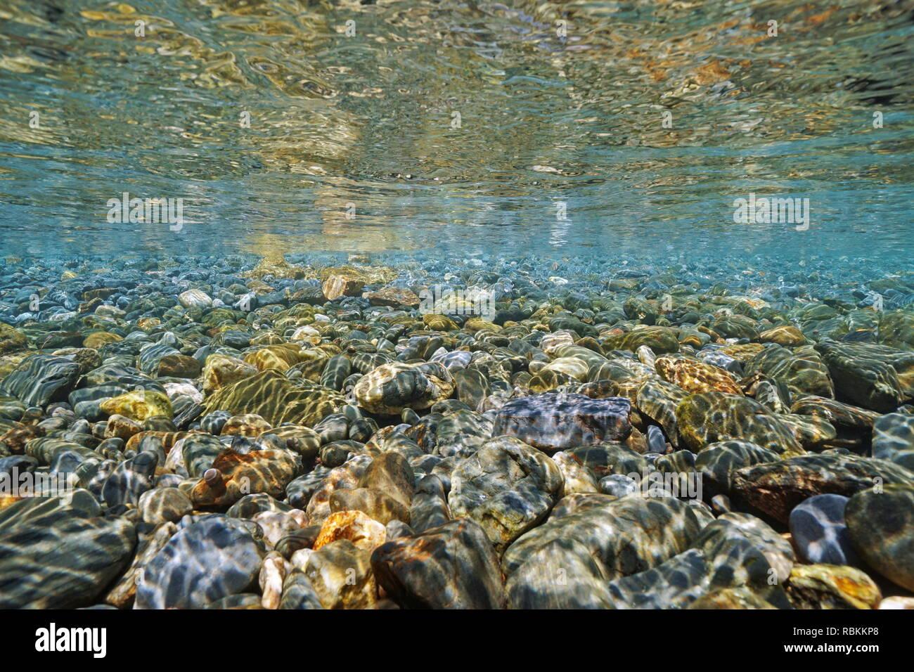 Pebbles underwater below water surface on the seashore, Mediterranean sea, France - Stock Image